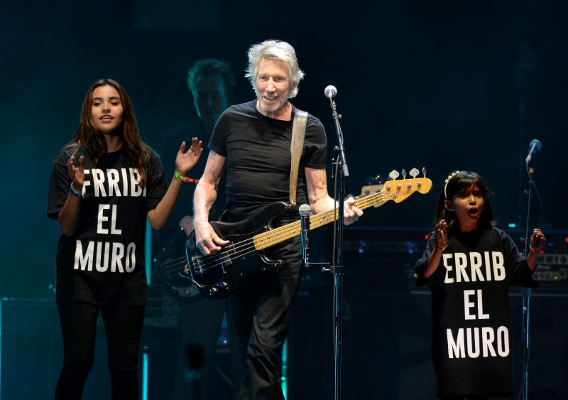 INDIO, CA - OCTOBER 16: Musician Roger Waters (C) performs with a children's choir wearing T-shirts saying 'derriba el muro' (tear down the wall) during Desert Trip at The Empire Polo Club on October 16, 2016 in Indio, California. (Photo by Kevin Mazur/Getty Images for Desert Trip)