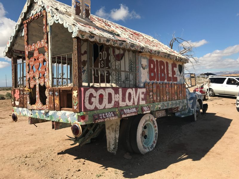 An old truck decorated with a ton of paint near Salvation Mountain