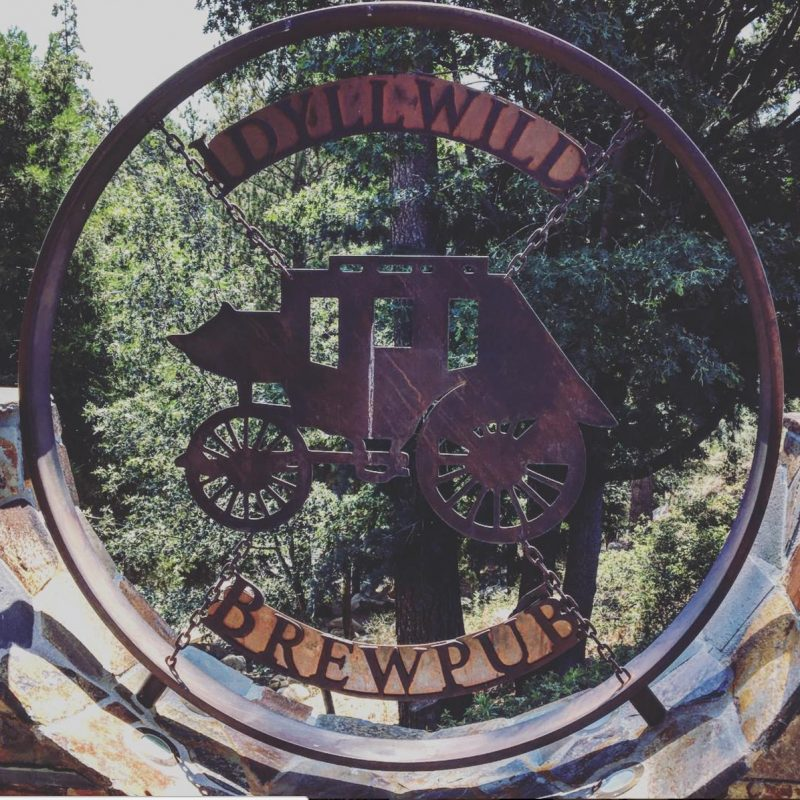 A sign showing a stagecoach at the entrance to the Idyllwild Brewpub
