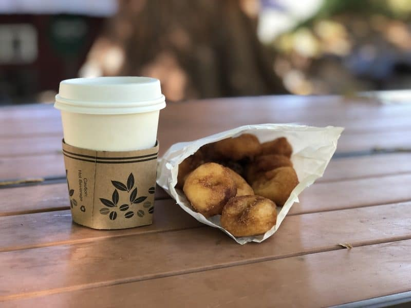 A bag of a dozen apple cider donuts and a cup of hot apple cider in Oak Glen California